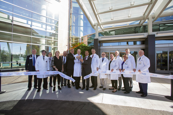 lanked by leaders from the University of Florida, UF Health and others, Ed Jimenez, CEO of UF Health Shands, has the honor of snipping the ribbon. Photo by Mindy Miller