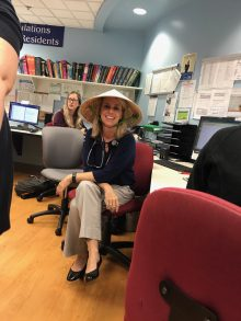 "Lindsay Thompson, M.D., shown with a hat given to her by her residents to shield her face from the sun during her other life as a so-called ""soccer mom."""