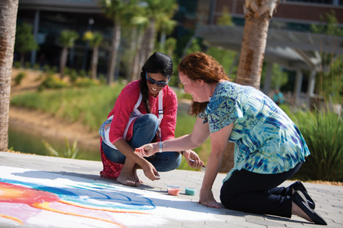 As part of this year's celebration of National Nurses Week, May 6-12, Anupama Priyardarshini, left, a member of the UF Health Shands Arts in Medicine program, created a mandala in the Garden of Hope outside the UF Health Heart & Vascular and Neuromedicine hospitals. Priyardarshini used Rangoli, a type of Indian folk art that involves colored sand and spices, to make the mandala's unique designs. — Greg Hamilton