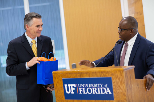 At a farewell dinner in his honor, Michael Good, M.D., left, the outgoing dean of the UF College of Medicine, accepts a bag of gifts and best wishes from Joseph A. Tyndall, M.D., M.P.H., the interim dean of the college.