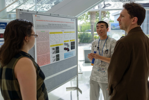 "Yi Sheng, Ph.D., (center) a postdoctoral associate in the University of Florida College of Medicine's department of aging and geriatric research, talks about his poster presentation outlining some of his aging-related scientific work. Sheng was one of several dozen participants in the UF Institute on Aging's eight annual ""Spotlight on Aging Research"" event at the Clinical and Translational Research Building that included researchers from several UF colleges, including Medicine, Pharmacy and Engineering, among others."