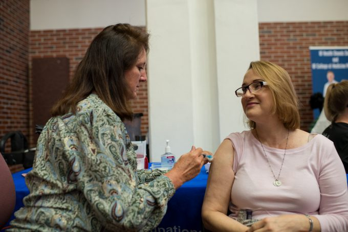Nicole Iovine, M.D., Ph.D., a UF Health infectious disease expert, practices what she preaches about preventing the flu virus from spreading by getting her flu shot in the UF Health Shands Hospital Atrium.
