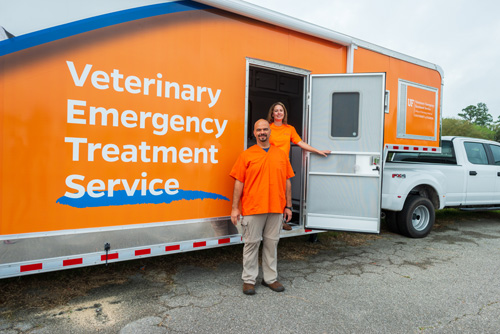 Larry Garcia, D.V.M., and Brandi Phillips, both of the UF Veterinary Emergency Treatment Service, stand with a new 44-foot mobile command and infrastructure support truck and trailer donated by the Banfield Foundation and PetSmart Charities that UF VETS will use during emergency deployments.