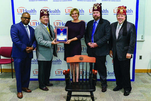 Laurel Blakemore, M.D., accepts the Shriners Professorship in Pediatric Orthopaedics from members of the organization as Joseph A. Tyndall, M.D., M.P.H., interim dean of the UF College of Medicine, looks on from left.